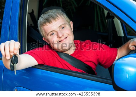 Close up portrait of young car driver with down syndrome showing car keys. Young man sitting behind steering wheel with safety belt fastened.