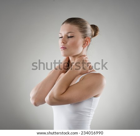 Close-up portrait of young Caucasian woman massaging her painful nape. Neck and back stretch concept.     - stock photo