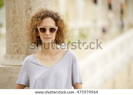 Close-up portrait of young confident woman wearing sunglasses and smiling.