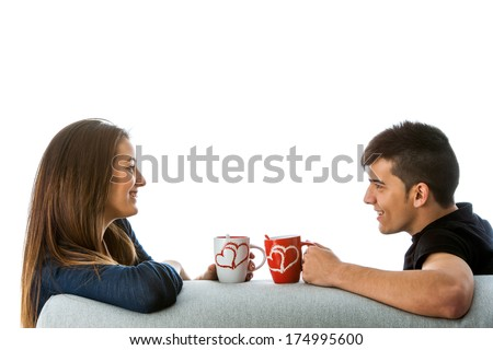 Close up portrait of young couple drinking coffee on couch.Isolated on white background.  - stock photo