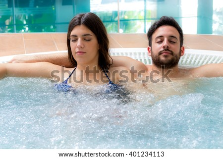 Close up portrait of young couple enjoying hot jacuzzi in hotel spa.