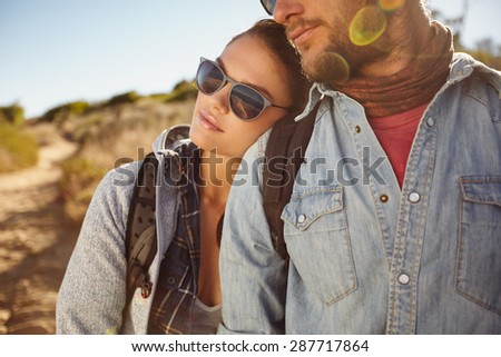 Close up portrait of young couple in love outdoors on a country hike. Young woman leaning on shoulder of her boyfriend. Caucasian couple hiking in nature. - stock photo