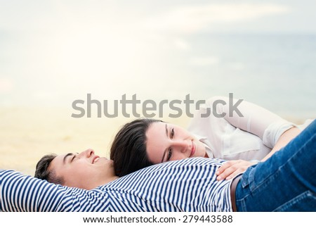 Close up portrait of Young couple laying together outdoors.Girl resting with head on boyfriend - stock photo