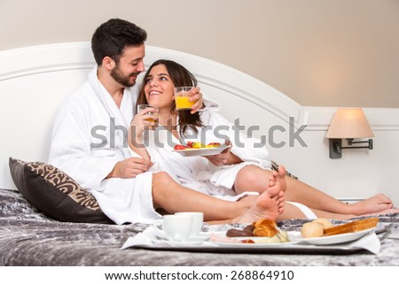 Close up portrait of Young couple on honeymoon in hotel room. Couple enjoying room service with breakfast tray. - stock photo