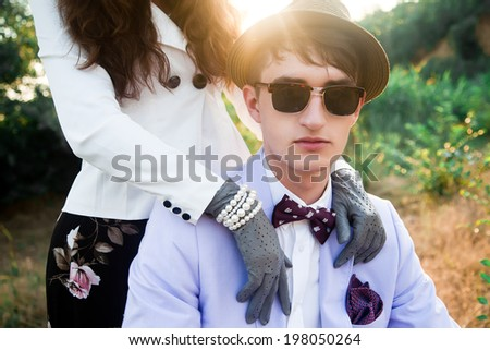 Close up portrait of young couple posing outdoor in part in retro stylish outfit. Young man wearing hat sunglasses and lavender suit. - stock photo