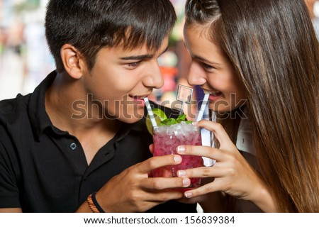 Close up portrait of young couple sharing fruit cocktail. - stock photo