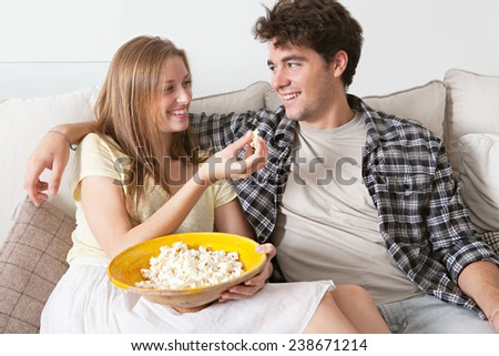 Close up portrait of young couple sitting together on a white sofa at home watching television, smiling eating pop corn enjoying a night in together. Home lifestyle and entertainment technology. - stock photo