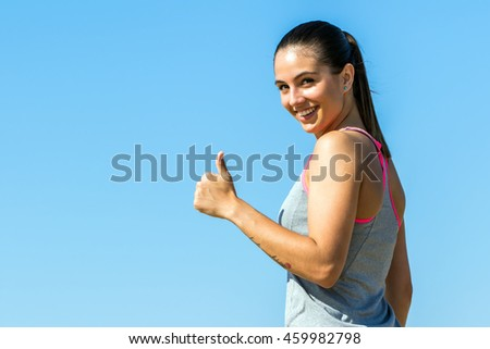 Close up portrait of young fitness girl doing thumbs up outdoors.