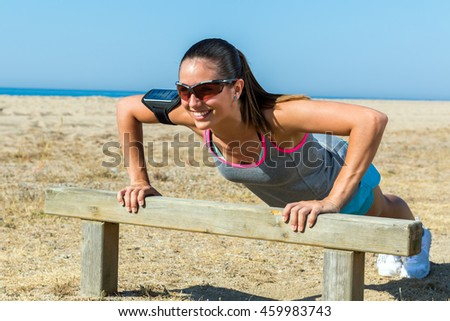 Close up portrait of young girl doing push-ups on wooden structure at sea side.