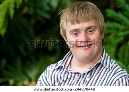 Close up portrait of young handicapped man with green leaves in background. - stock photo