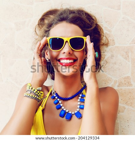 Close up portrait of young happy smiling brunette woman laying at the sun, enjoy her vacation and hot days, wearing bright stylish bikini and sunglasses. Laughing and having fun alone. - stock photo