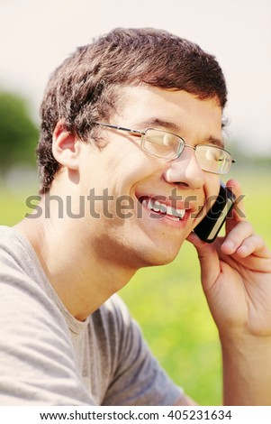 Close up portrait of young hispanic man wearing glasses and t-shirt, sitting in spring park outdoors, holding mobile phone near his head and smiling - communication concept - stock photo