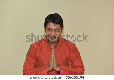 Close up portrait of Young Indian Man wearing Ethnic Indian Dress, Man is welcoming by joining his hands, Indian Style Welcoming gesture known as Namaste, lot of space for text messages in the picture - stock photo