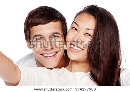 Close up portrait of young interracial couple, hispanic man and asian girl, hugging, smiling attractive healthy toothy smile and taking selfie isolated on white background - dental care concept - stock photo