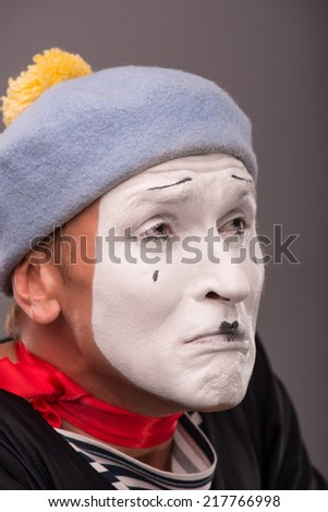 Close-up Portrait of young male mime with white face, grey hat crying with tears and looking aside  isolated on grey background with copy place - stock photo