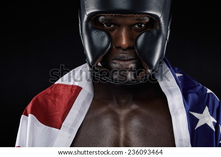 Close-up portrait of young male wearing boxing helmet with american flag against black background - stock photo