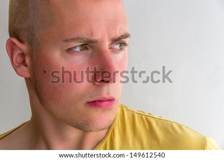 Close-up portrait of young man with a frown, serious and looking to the side, with yellow shirt   - stock photo