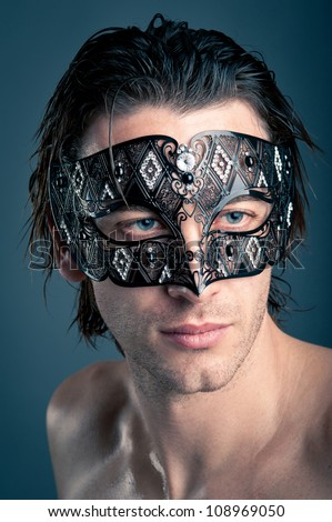 Close up portrait of young man with carnival mask against dark background. - stock photo
