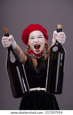 Close-up Portrait of young mime girl holding big bottles in her hands joyfully shouting and looking at the camera and showing bottles to you isolated on grey background  - stock photo