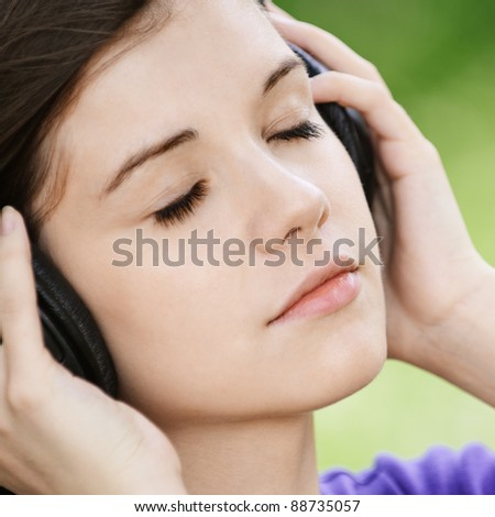 Close-up portrait of young pensive woman listening to music at summer green park. - stock photo
