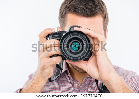 Close up portrait of young photographer taking photo - stock photo