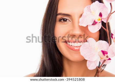 Close up portrait of young pretty woman covering half of her face with orchid