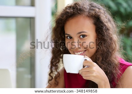 Close up portrait of young pretty woman drinking coffee - stock photo