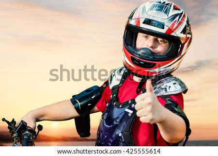 Close up portrait of young quad bike rider with down syndrome doing thumbs up on bike. - stock photo