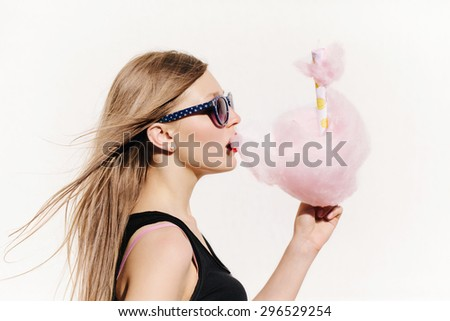 Close up portrait of young sexy woman eating pink cotton candy. Lifestyle portrait. White background, not isolated - stock photo