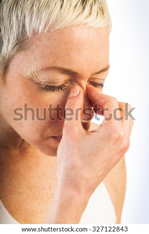 Close up portrait of young sick woman having flu or sinus infection  isolated on white background. Health care concept. Studio shot.