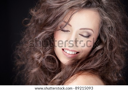 close-up portrait of young smiling brunette, shallow DOF, clear focus on model's eye - stock photo