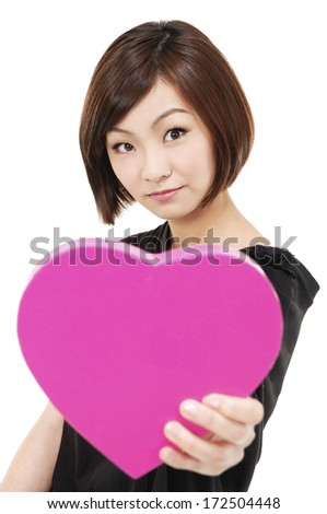 Close up portrait of young smiling female holding heart gift box - stock photo