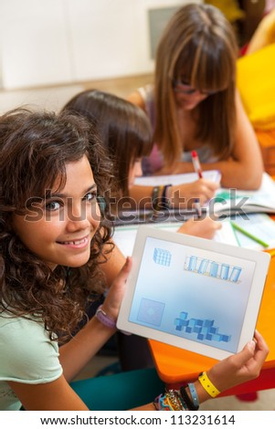 Close up portrait of young student at desk showing  homework on digital tablet. - stock photo
