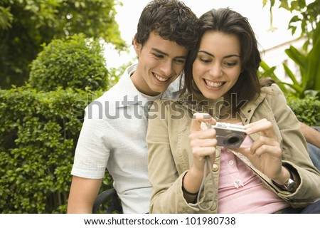 Close up portrait of young tourist couple looking at pictures on their digital photo camera.