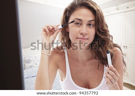 close up portrait of young woman doing make up - stock photo
