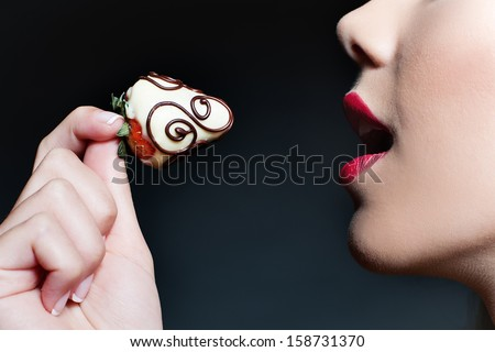Close-up portrait of young woman eating delicious strawberry covered with white chocolate - stock photo