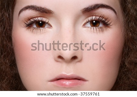 Close-up portrait of young woman face with clear makeup, focus on eyes