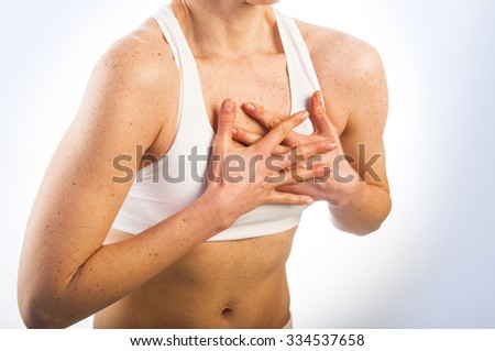 Close up portrait of young woman having heart attack, on white background - stock photo