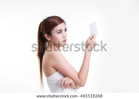 Close-up portrait of young woman holding credit card and looking at it isolated on white background - stock photo
