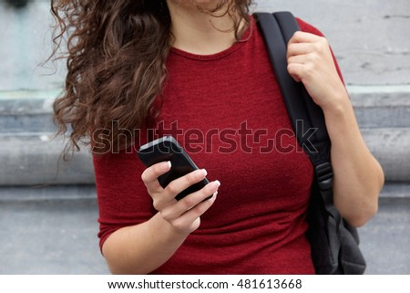 Close up portrait of young woman holding mobile phone in hand