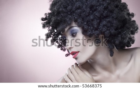 Close up portrait of young woman in afro wig on gray back