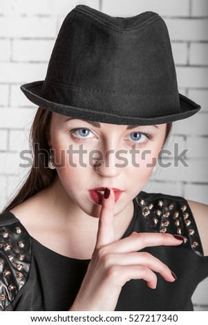 Close-up portrait of young woman in hat placing finger on lips, gestures silently, quiet, shhh, secret, facial expression, human emotions, signs and symbols