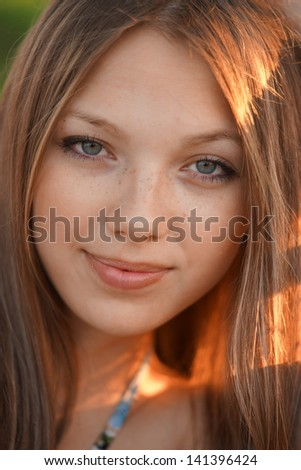close up portrait of young woman in the park - stock photo