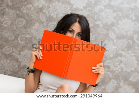 Close up portrait of young woman lying on bed and hiding behind a book in hotel room. - stock photo