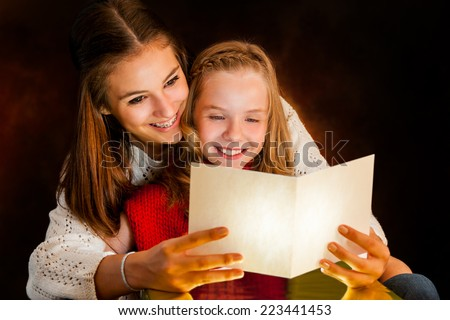 Close up portrait of young Woman reading Christmas card to youngster.