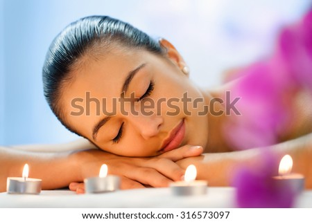 Close up portrait of Young woman relaxing in dimmed candle light after massage.