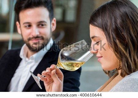 Close up portrait of young woman smelling white wine aroma at tasting. - stock photo