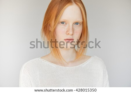 Close up portrait of young woman with red hair and blue eyes looking at the camera with serious expression on her face. Beautiful teenage girl with perfect healthy freckled skin wearing white top  - stock photo