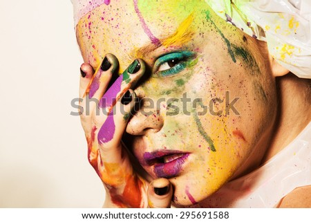 Close-up portrait of young woman with unusual makeup. Model posing with paint drops over her face. Creative makeup. - stock photo