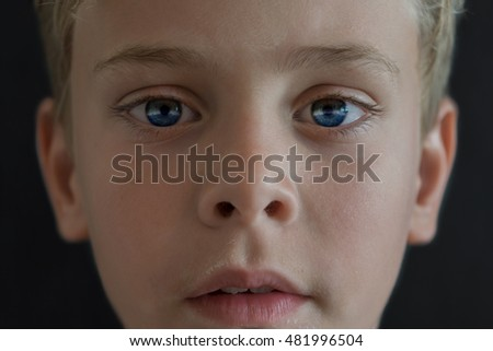 Close up portrait of young wondering blonde boy in space with planet earth reflection and stars in his eyes. Detail photo of blonde child. Elements of this image furnished by NASA